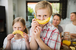 Brother and sister having fun with two bananas