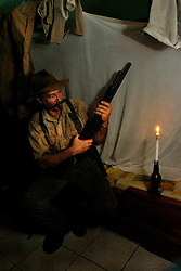 Dairen Simpson checks his shotgun that he must use ofr protection when he checks the traps inside his room in Lindi, Tanzania. Ami Vitale