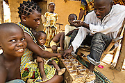 A man and teenage girl play a local game called awale (owari) outside their home in the village of Ligaleu, Cote d'Ivoire on Wednesday May 4, 2011.