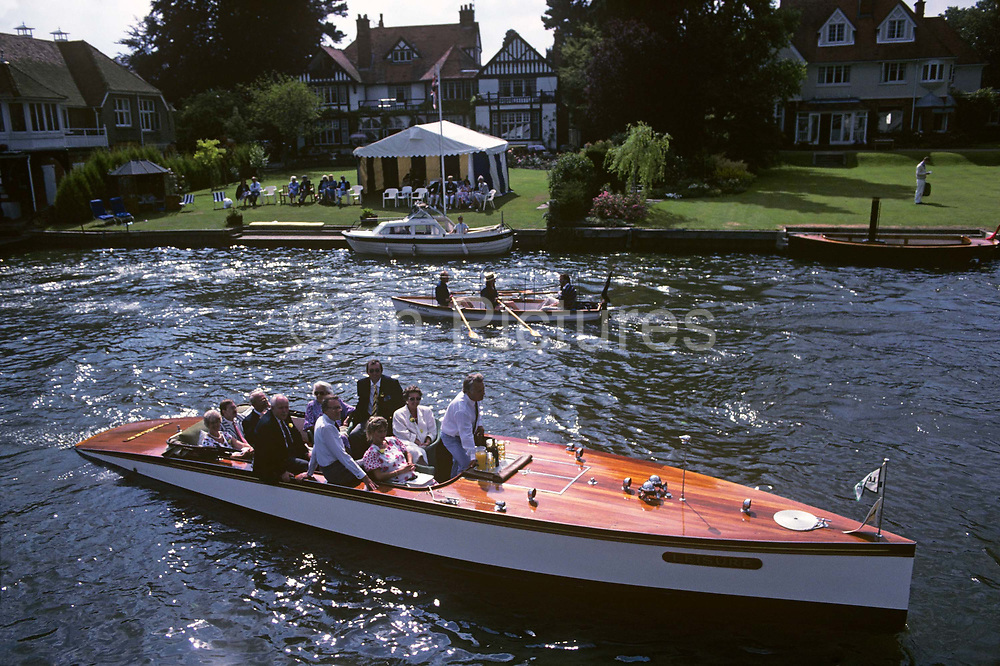 Well-dressed and well-appointed English people pass-by on the River Thames during the Henley Royal Regatta boat races, England. In the foreground is a smart and highly-polished launch filled with a party of friends who motor past while to their port (left) a rowing boat with three men in blazers pass them going downstream. On the riverbank a garden marquee hosts another social gathering. In 1829 a boat race challenge was held between teams representing the universities of Oxford and Cambridge. The venue chosen was a straight stretch of the Thames at the small town of Henley-on-Thames. Now held July and is one of the main dates on the sporting calendar and social season for the hoi polloi