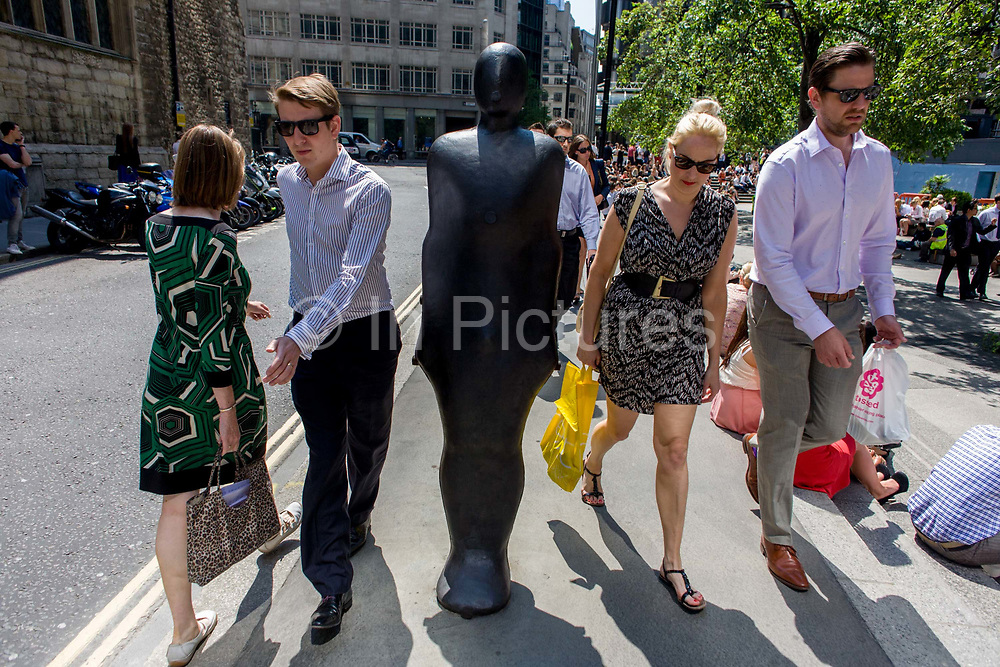City of London office workers pass one of a pair of leaning figures by Anthony Gormley entitled Parralel Field (1990), part of Sculpture in the City, a summer street art exhibition in the Square Mile, the capital's financial district. Antony Mark David Gormley, OBE, RA (born 30 August 1950) is a British sculptor. His best known works include the Angel of the North, a public sculpture near Newcastle upon Tyne in the North of England, commissioned in 1994 and erected in February 1998.