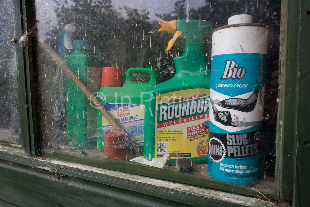 A detail of a green, wooden garden shed's domestic chemicals lined-up on the sill inside. We see through the window, slug pellets, weedkiller and stain remover - all household products that are dangerous to the young and so remain out of reach to small hands.