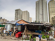 04 SEPTEMBER 2013 - BANGKOK, THAILAND: Men drink beer and relax at a makeshift bar on the construction site of a new high rise apartment / condominium building on Soi 22 Sukhumvit Rd in Bangkok. Most of the workers at the site are Cambodian immigrants.    PHOTO BY JACK KURTZ
