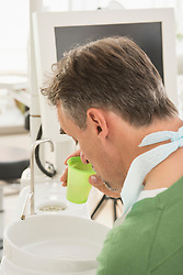 Dental patient spitting into a cuspidor in the dentists office, Munich, Bavaria, Germany