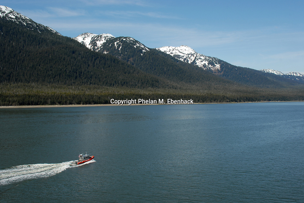 A United States Coast Guard boat escorts a cruise ship through the Gastineau Channel to Juneau, Alaska, with Douglas Island in the background. (Photo by Phelan M. Ebenhack)
