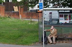 Elderly man wearing a face mask during Coronavirus pandemic waiting for a bus to take him into Central Reading, UK September 2020