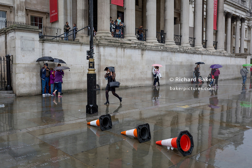 Families shelter beneath umbrellas during a sudden downpour outside the National Gallery in Trafalgar Square, on 13th August 2018, in London, England.