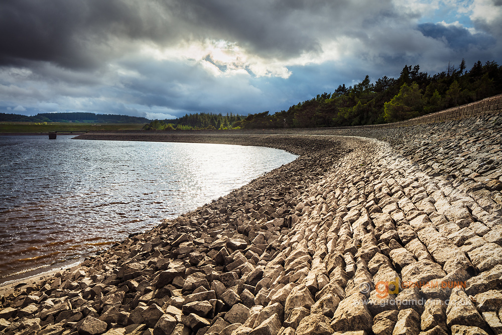 A moment of brilliant light amidst dramatic clouds and stormy skies over Redmires Lower Reservoir in Sheffield and the Peak District National Park.