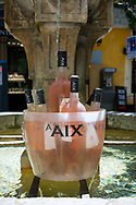 Bottles of local wine are kept cool in a public fountain outside a restaurant  in Aix-en-Provence, France