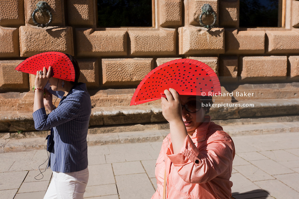 Two women tourists from Asia walk in the sunshine at Alhambra, both holding red fans to shield their faces.