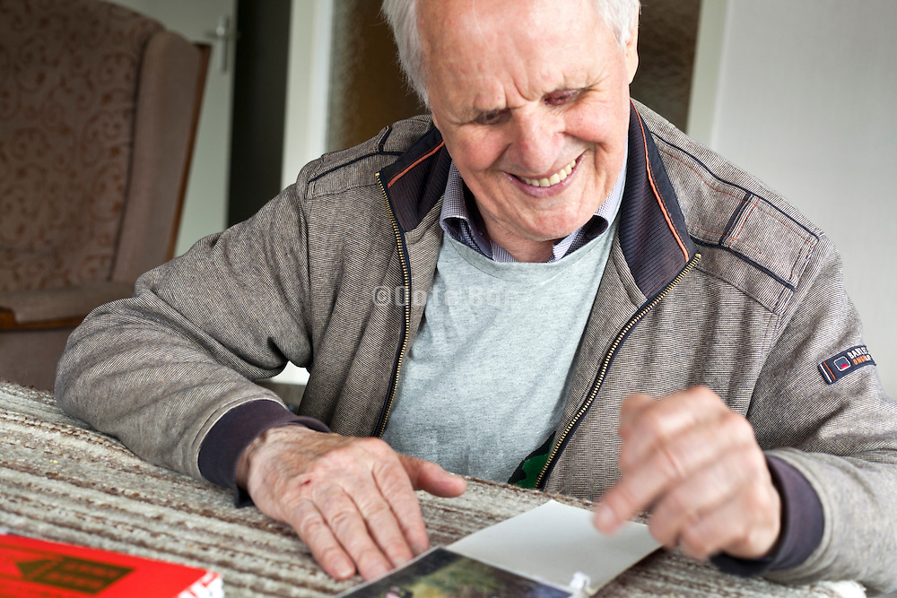 happy smiling elderly man sitting at the table with photo album