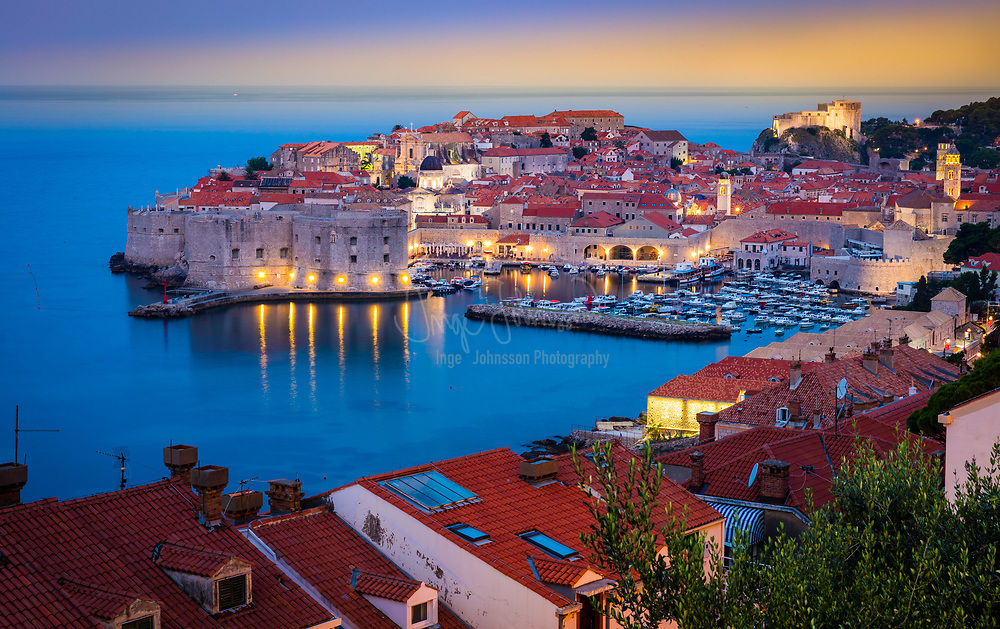 Predawn light over Dubrovnik, Croatia, with its characteristic medieval city walls. Dubrovnik is a Croatian city on the Adriatic Sea, in the region of Dalmatia. It is one of the most prominent tourist destinations in the Mediterranean, a seaport and the center of Dubrovnik-Neretva County. In 1979, the city of Dubrovnik joined the UNESCO list of World Heritage Sites.<br /> <br /> The prosperity of the city was historically based on maritime trade; as the capital of the maritime Republic of Ragusa, it achieved a high level of development, particularly during the 15th and 16th centuries, as it became notable for its wealth and skilled diplomacy.<br /> <br /> A feature of Dubrovnik is its walls that run almost 2 km (1.24 mi) around the city. The walls run from four to six meters (13.2 to 19.8 feet) thick on the landward side but are much thinner on the seaward side. The system of turrets and towers were intended to protect the vulnerable city. The walls of Dubrovnik have also been a popular filming site for the fictional city of King's Landing in the HBO television series, Game of Thrones.