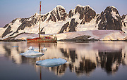 Expedition yacht Pelagic Australis moored in bay near Pleneau and Hoovgard Islands - alpenglow reflection of peaks on Booth Island behind - Antarctic Peninsula March 2020