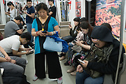 Whether in the rush hour or during quiet times, everyone spends their whole day continuously using, watching or interacting with their mobile telephones. Hardly any conversation, and little contact with strangers. Beijing, China