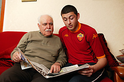 Grandfather and grandson at home sitting and reading a newspaper together,