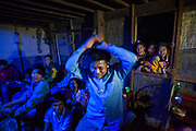 A young man shows off his moves at a party in Ban Huay Phouk, Laos as other partygoers, and young girls in the window, watch. The celebration was hoped to bring good luck to the woman of the house, who was suffering from cancer and whom modern western medicine had failed to treat.