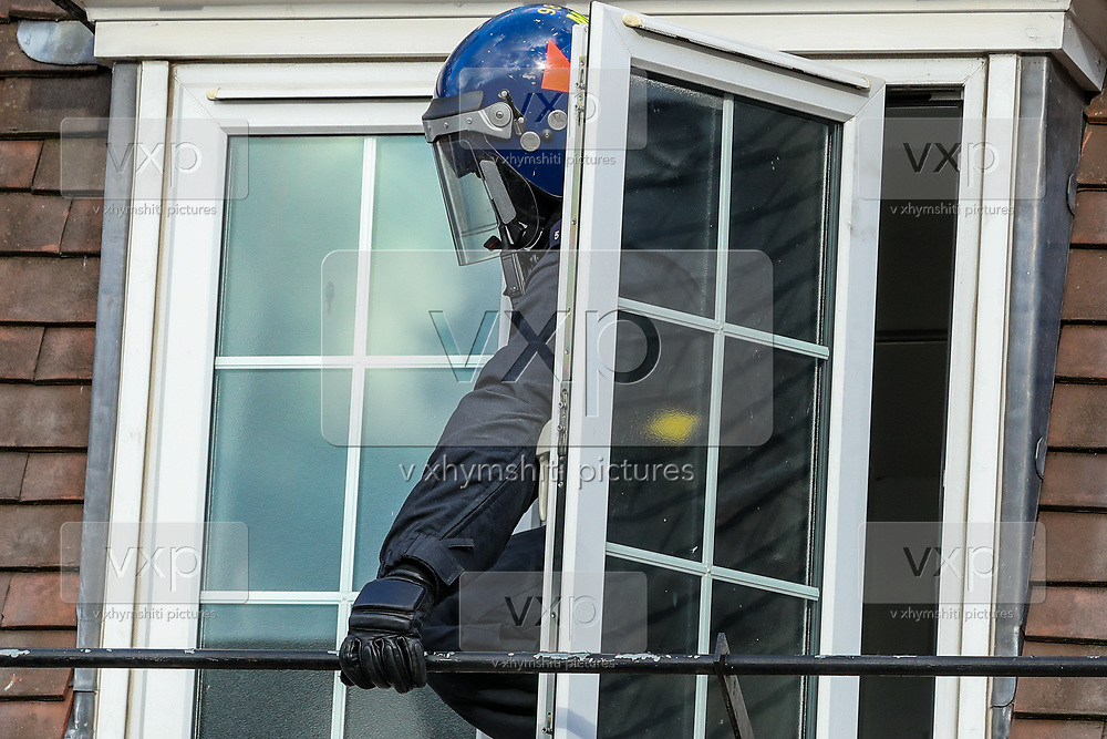 A police officer is seen reaching out at a roof-top through another Flat's window as a measure of safety to prevent the alleged suspected fugitive from possibly fleeing his flat. A man who is alleged to have assaulted members of the public and emergency worker in south London on  Tuesday, Aug 18, 2020, didn't respond to multiple calls by the police to surrender.<br /> Members of the MET police crew stormed into his barricaded doorstep after Martin wouldn't respond to their multiple calls to surrender as he was declared that he was going to be arrested.<br /> After breaking the door police stumbled into a barricade made of a ladder, washing machine, several chairs and other wood and plastic items. After forcing themselves into his apartment, police couldn't find him. The search is on-going. (VXP Photo/ Vudi Xhymshiti)
