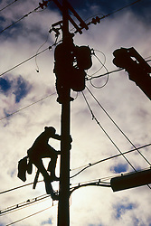 Stock photo of Two linemen climbing an electrical pole for repairs