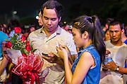 22 NOVEMBER 2013 - BANGKOK, THAILAND: A couple on a date use their smart phones at a Prathom Bunteung Silp mor lam show in Bangkok. Mor Lam is a traditional Lao form of song in Laos and Isan (northeast Thailand). It is sometimes compared to American country music, song usually revolve around unrequited love, mor lam and the complexities of rural life. Mor Lam shows are an important part of festivals and fairs in rural Thailand. Mor lam has become very popular in Isan migrant communities in Bangkok. Once performed by bands and singers, live performances are now spectacles, involving several singers, a dance troupe and comedians. The dancers (or hang khreuang) in particular often wear fancy costumes, and singers go through several costume changes in the course of a performance. Prathom Bunteung Silp is one of the best known Mor Lam troupes in Thailand with more than 250 performers and a total crew of almost 300 people. The troupe has been performing for more 55 years. It forms every August and performs through June then breaks for the rainy season.     PHOTO BY JACK KURTZ