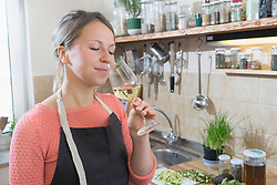 Young women smelling white wine in kitchen,