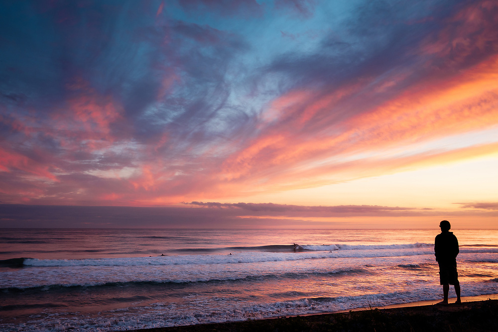 Man watching surfers catching the waves at St Ouen's Bay, under the purple pink sky after sunset in Jersey, Channel Islands