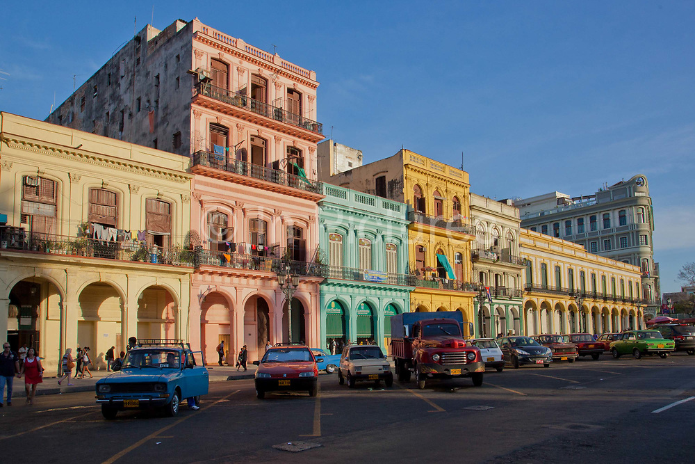 Colourful houses on the promenade in the centre of old Havana, outside the Capitolio building, with beautifully preserved old Amercian cars in front, the classic iconic image of Havana, Cuba.