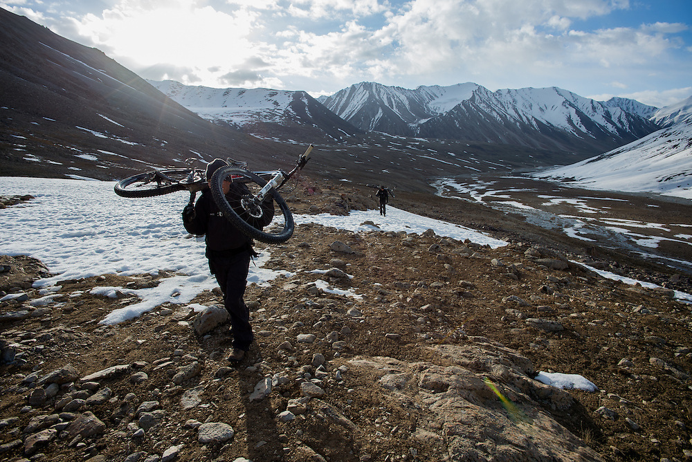 """Colin """"CJ"""" Jones, carries his bike up the 4867m Shawal Pass at 05.25 am. Early, pre-dawn starts, usually at 4.30 a.m. enabled us and our horses to cross the snowpack while still frozen."""