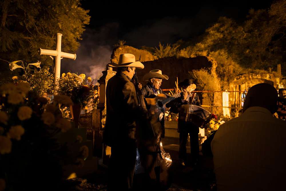 """During Day of the Dead celebrations (""""Día de los Muertos"""" in Spanish), musicians play their instruments and sing at a cemetery in Xoxocotlán, on the outskirts of Oaxaca, Mexico."""