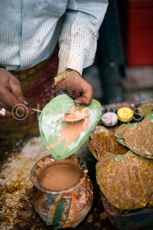 """A man making paan, in the Bapu bazaar, Jaipur, India<br /> Paan consists of chewing Betel leaf (Piper betle) combined with the areca nut. It is chewed as a palate cleanser and a breath freshener. It is also commonly offered to guests and visitors as a sign of hospitality and as an """"ice breaker"""" to start conversation. It also has a symbolic value at ceremonies and cultural events in south and southeast Asia. Paan makers may use mukhwas or tobacco as an ingredient in their paan fillings. Although most types of paan contain areca nuts as a filling, some do not. Other types include what is called sweet paan, where sugar, candied fruit and fennel seeds are used."""