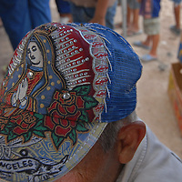 Aug 12, 2010 - Reynosa, Mexico - As residents of the colonia Satelite Uno gather under the distribution tents, one of the Frank Ferree Border Relief volunteers sits taking a break from the heat. On his hat the Lady of Guadalupe or the  virgin mary one of the most popular religious figures in Mexico..(Credit Image: © Josh Bachman/ZUMA Press)