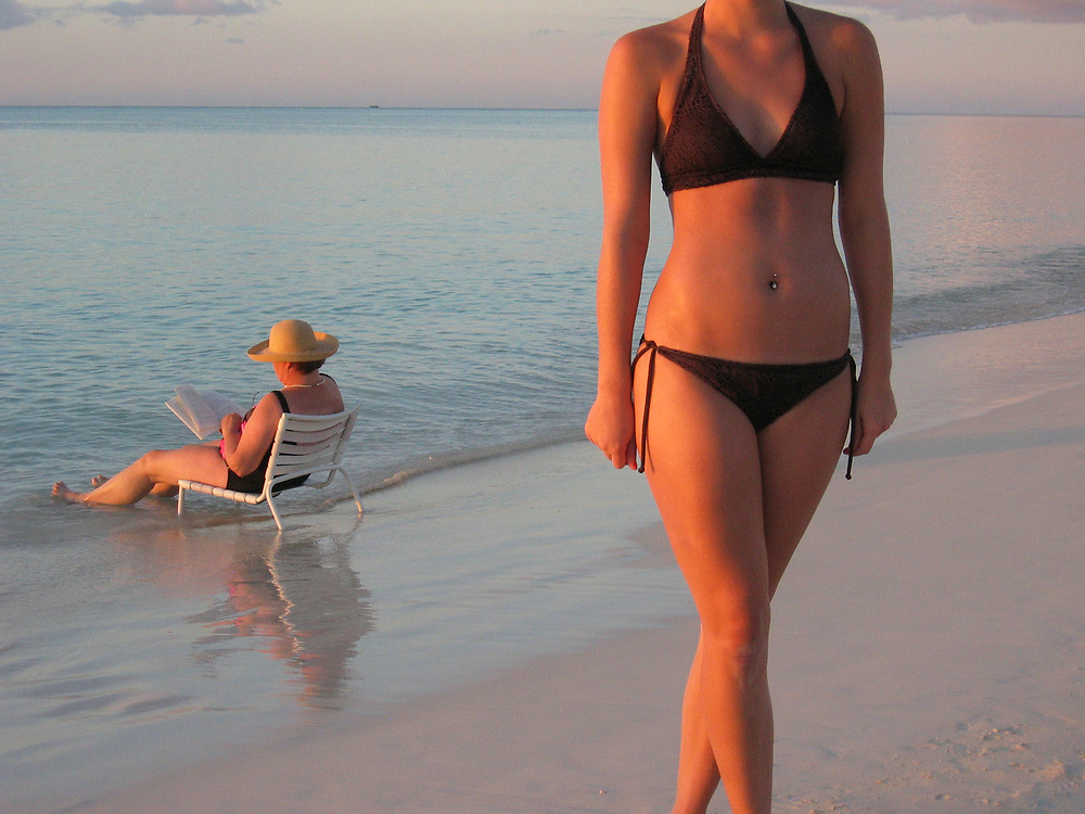 Woman on beach at sunset with older woman wearing a straw hat, sitting in beach chair in surf, and reading a paper