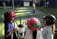 Chester, New York  - Young softball players talk while waiting to take a turn at batting in the cage with the video simulator during the first anniversary open house celebration at The Rock Sports Park on Nov. 12, 2011.