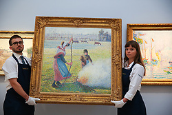 © Licensed to London News Pictures. 29/01/2020. London, UK. Technicians prepare to hang Camille Pissarro's painting titled Gelée Blanche, Jeune Paysanne Faisant Du Feu (est £8m to £12m) at the preview of Sotheby's Impressionist, Modern and Surrealist art sales. The auction will take place at Sotheby's in central London on 4 and 5 February 2020. Photo credit: Dinendra Haria/LNP