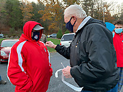 """Phil Hawkins receives his """"I voted"""" sticker from local Oneida Township committee member Jim Blow."""