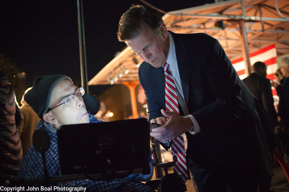 Don Beyer speaks with supporter, Gordon Richmond, who suffers from Cerebral Palsy and communicated with his specialized computer, following a Democrat get out the vote (GOTV) rally at Market Square in Old Town Alexandria, VA, on  Monday, November 3, 2014, the day before Election Day.  Beyer is running as a candidate to replace Jim Moran in the 8th District (VA).  John Boal Photography