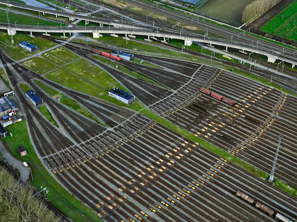 Nederland, Zuid-Holland, Zwijndrecht, 25-02-2020; Kijfhoek, rangeerterrein voor goederentreinen. Overzicht van de verdeelsporen en railremmen. Kijfhoek huisvest Keyrail, exploitant Betuweroute en is in beheer bij ProRail. De Betuweroute, die begint als Havenspoorlijn op de Maasvlakte, verbindt via Kijfhoek de Rotterdamse haven met het achterland. Het rangeeremplacement dient voor het sorteren van goederenwagons waarbij gebruik gemaakt wordt van de zwaartekracht, het 'heuvelen': de wagons worden de heuvel opgeduwd, bij het de heuvel afrollen komen ze, door middel van wissels, op verschillende verdeelsporen. Railremmen zorgen voor het automatisch remmen van de wagons. Na het heuvelproces staan de nieuw samengestelde treinen op aparte opstelsporen.<br /> Kijfhoek, railway yard (train shunting-yard) used by ProRail and Keyrail (Betuweroute operator). Kijfhoek connects via the Betuweroute (beginning as Havenspoorlijn on the Maasvlakte), through the port of Rotterdam with the hinterland. The shunting yard for sorting wagons makes use of gravity. The new trains are assembled on separate tracks.<br /> luchtfoto (toeslag op standard tarieven);<br /> aerial photo (additional fee required)<br /> copyright © 2020 foto/photo Siebe Swart