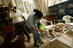 Alyaa Abdul Hassan Abbood, 23, a translator, fixes dinner while her brother Ali Abdul Hassan Abbood, talks on the phone, Baghdad, Iraq, Sept. 28, 2003. Abbood works with the U.S. military to mediate as Iraqi civilians come in to receive monetary compensation for damages done by American troops in Baghdad.