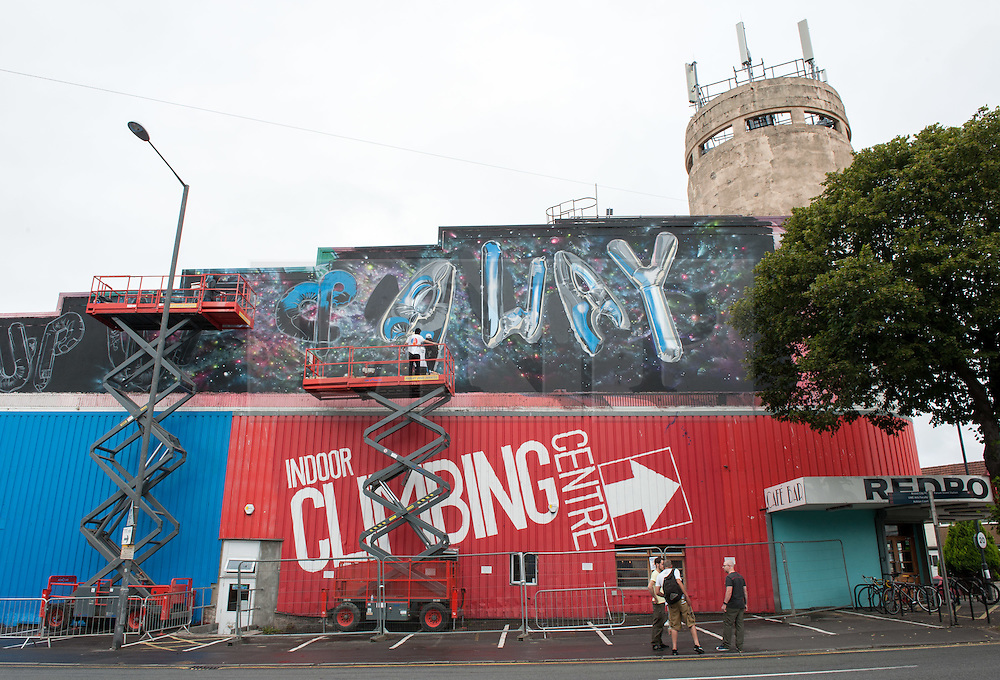 """© Licensed to London News Pictures. 24/07/2016. Bristol, UK.  """"Up Up & Away"""" by Cheba Bristol and Fanakapan, on the side of the Red Point Climbing Centre at Upfest street art festival 2016, Europe's largest, free, street art & graffiti festival, attracting over 300 artists painting 28 venues throughout Bedminster & Southville, Bristol.  Photo credit : Simon Chapman/LNP"""