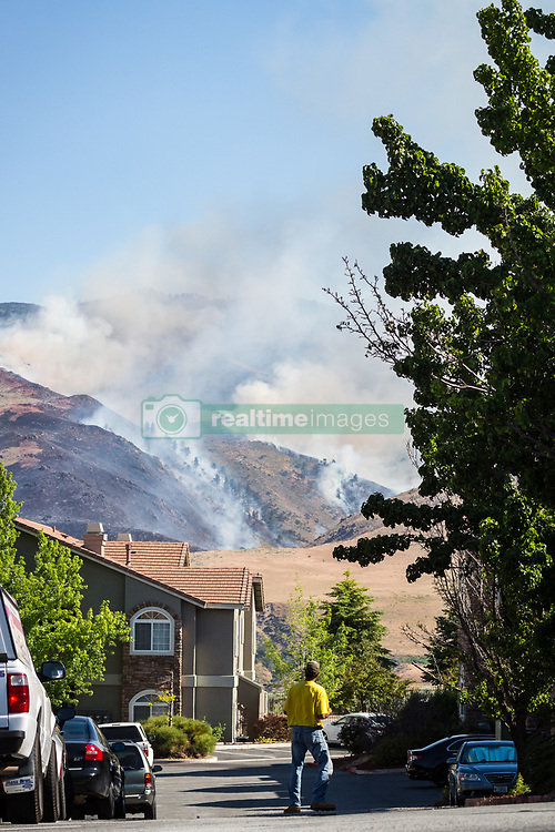 June 22, 2017 - Reno, Nevada, U.S - A spectator watches the Hunter Creek Fire from the Aviana at Tuscany apartment complex. The fire is burning just west of downtown Reno, Nevada, on U.S. Forest Service land. According to a Truckee Meadows Fire representative, the cause of the fire is not known, but the point of origin is known. The blaze is estimated at 250 acres and is approximately 35% contained. No structures have been damaged. (Credit Image: © Tracy Barbutes via ZUMA Wire)