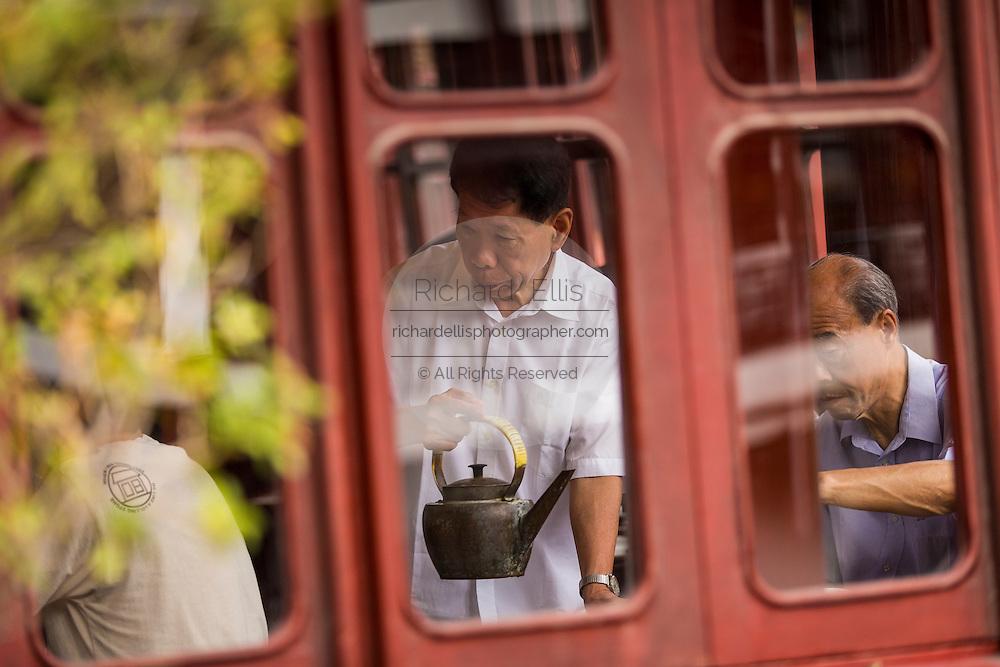 An attendant serves tea in the Huxinting Teahouse in Yu Yuan Gardens Shanghai, China