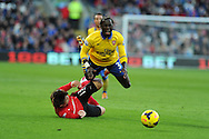Arsenal's Bacary Sagna is sent flying by a tackle from Cardiff's Kim Bo-Kyung. Barclays Premier League match, Cardiff city v Arsenal at the Cardiff city stadium in Cardiff, South Wales on Saturday 30th Nov 2013. pic by Andrew Orchard, Andrew Orchard sports photography,