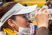 24 NOVEMBER 2012 - BANGKOK, THAILAND:  A woman tries to rinse tear gas out of her eyes after Thai riot police used tear gas on a large anti government, pro-monarchy, protest  on November 24, 2012 in Bangkok, Thailand. The Siam Pitak group, which sponsored the protest, cited alleged government corruption and anti-monarchist elements within the ruling party as grounds for the protest. Police used tear gas and baton charges againt protesters.       PHOTO BY JACK KURTZ