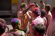 A man sprinkles gulal paint powder over another's head during the festival of Holi, in Udaipur, Rajasthan, India