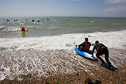 Instructor from a Brighton seafront kayak operator, pushes a rather large beginner out into the surf to join friends already at sea