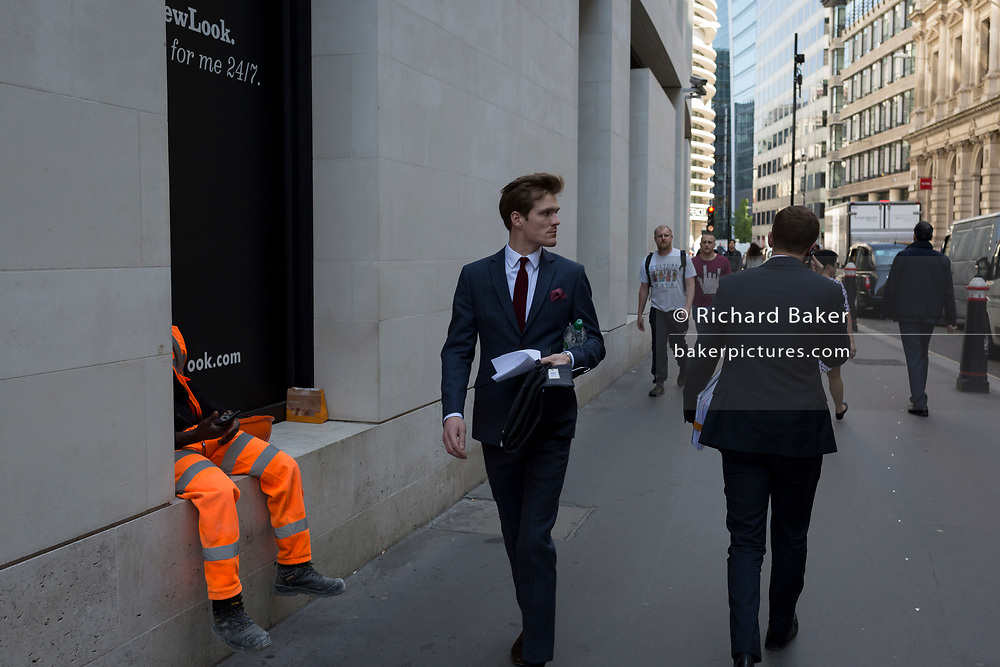 The legs of a workman wearing hi-vis and a City businessman in a suit walking down Lombard Street in the City of London, the capital's financial district aka the Square Mile, on 15th May 2018, in London, UK.