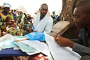 Vaccinator Bala Diakite (C) discusses records with intern Seyba N'Diaye (R) during a vaccination session in the village of Banankoro, Mali on Saturday August 28, 2010..