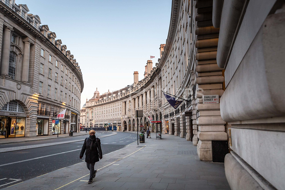 A woman walks up an eerily quiet Regent Street in the early evening at what would normally be rush hour in London on March 27th, 2020. The centre of London is extremely quiet with almost every business closed and very few people about because of the Governments lockdown measures due to the Coronavirus crisis.