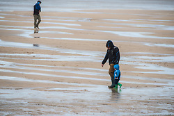 A father takes his son for a walk on a cold, windy  day at Fistral Beach in Newquay, Cornwall.
