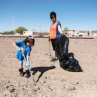 McKenzie Martinez, 5, left, and Maria Murrufo from the Lady Titans travel softball team volunteer at the Comcast Cares Community Cleanup Day by picking up trash on 9th Street, Saturday, May 4 in Gallup.