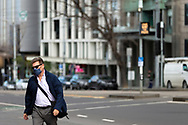 A man wearing sunglasses and a facemask walks towards parliament house during COVID-19. A further 238 Coronavirus cases have been discovered overnight, bringing Victoria's active cases to over 2000, speculation is rising that almost all of Victoria's current cases stem from the Andrews Government botched hotel quarantine scheme as well as the Black Lives Matter protest.  Premier Daniel Andrews warns that Victoria may go to Stage 4 lockdown if these high numbers continue. (Photo be Dave Hewison/ Speed Media)